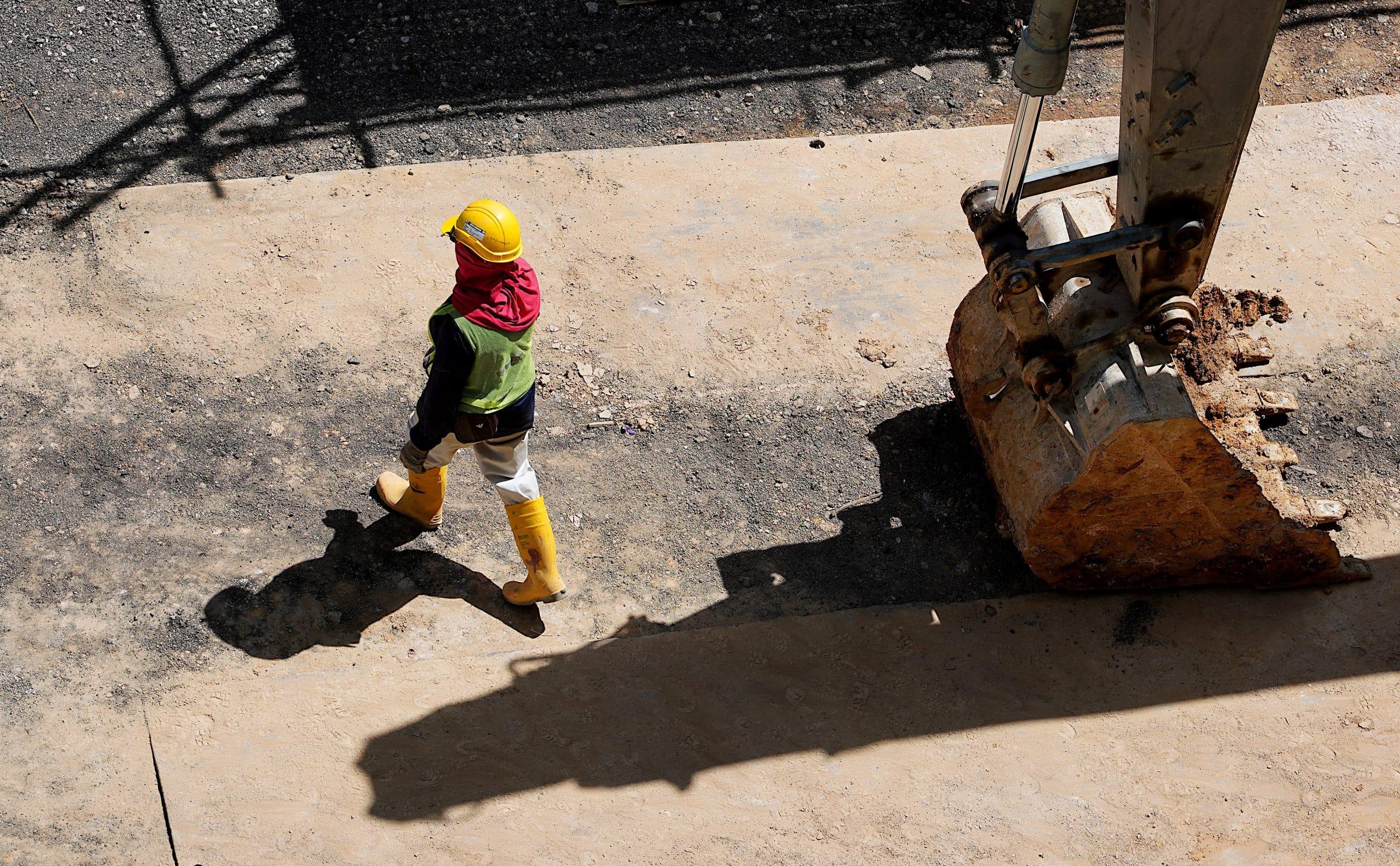 Opérateur engin de chantier a coté de sa pelle hydraulique